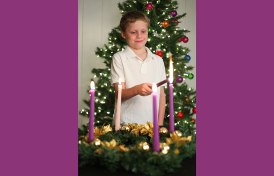 boy lighting Advent candles