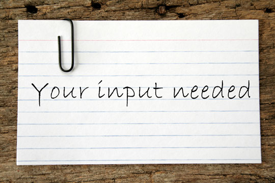 """Your input needed"" written on note card"
