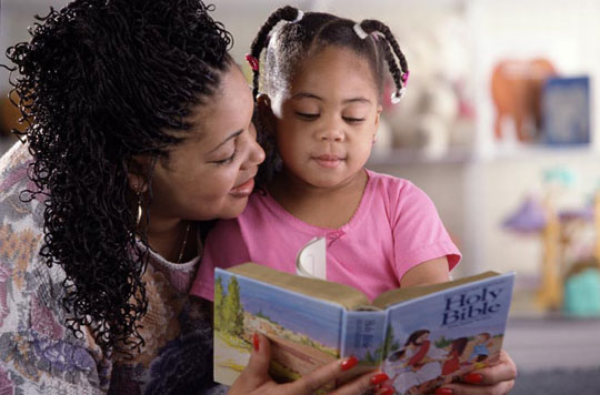 mother reading Bible with daughter