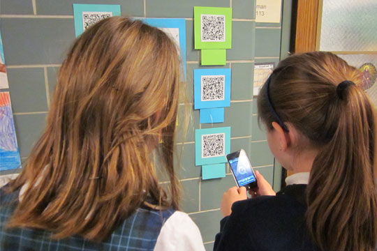 girls doing Easter QR codes activity
