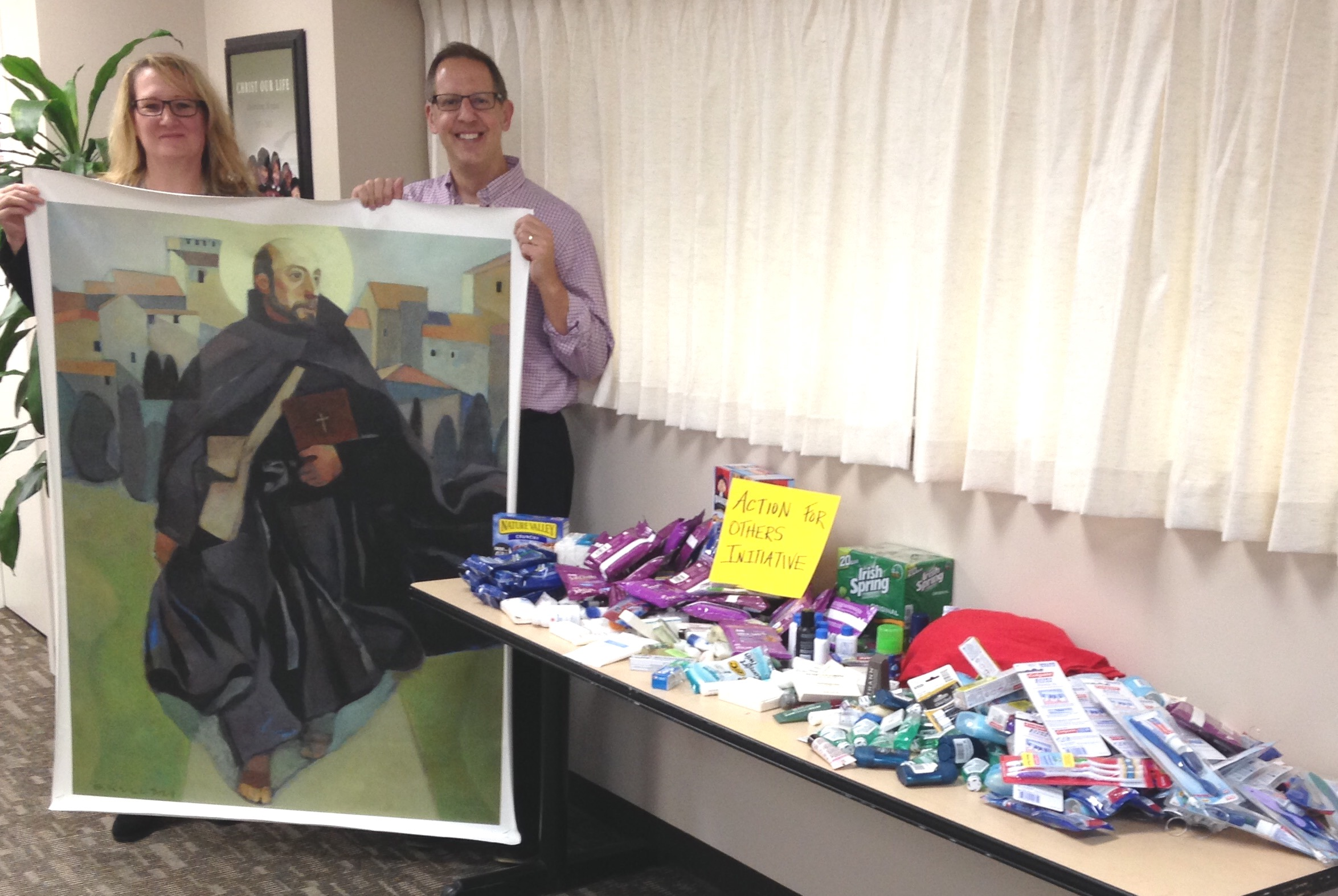 Here I am with St. Ignatius and Linnette Mathys who heads our Loyola Press Action for Others Initiative, alongside donated items for the care packages!