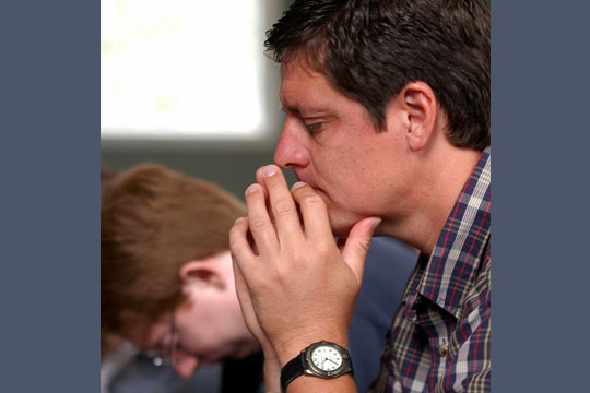 man praying with young person