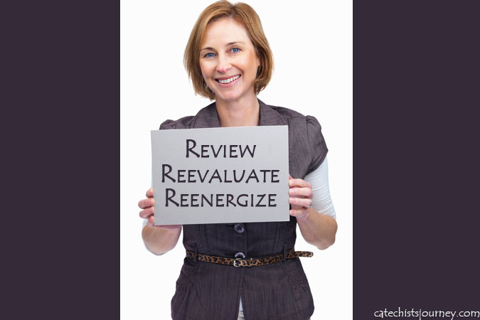 woman holding sign: Review, Reevaluate, and Reenergize