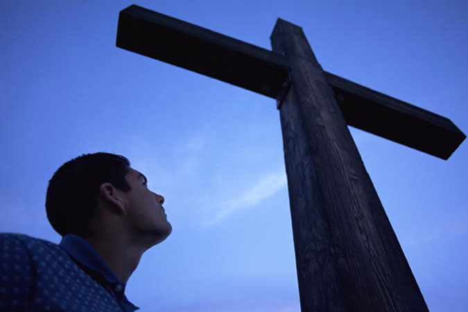 young man looking at cross