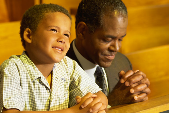 father and son praying in church