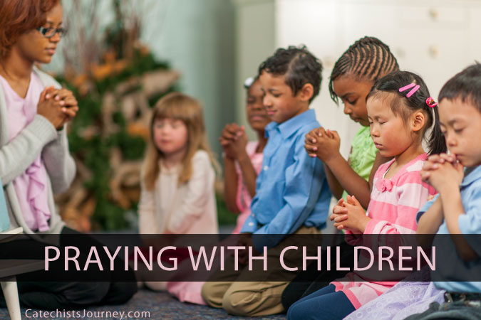 Catechist praying with children