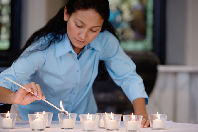 catechist preparing sacred space by lighting candles