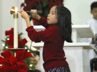 girl lighting candle at Christmas Mass