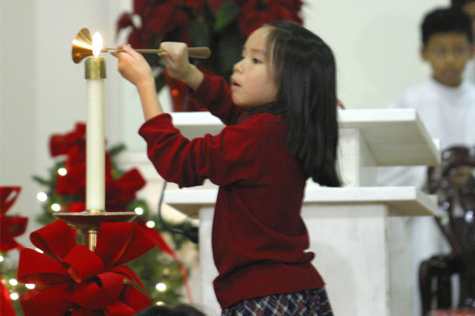 girl lighting candle at Christmas Mass