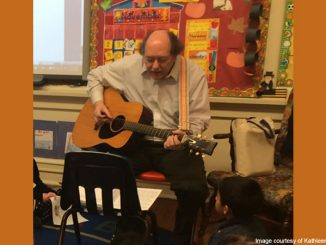 man playing guitar in classroom - image courtesy of Kathleen Butler