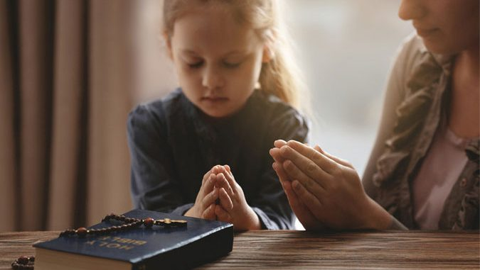 mother and daughter praying at home