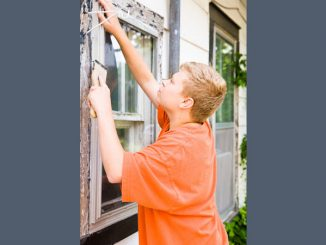 young man working on restoration of windows