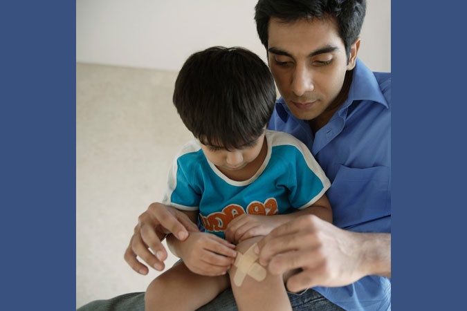 father helps son with bandage on knee