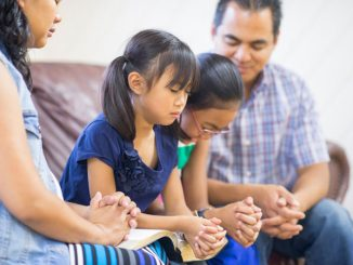 family praying on couch