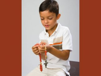 young boy praying the Rosary