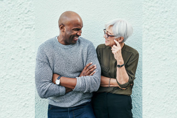 two adults talking while leaning against wall