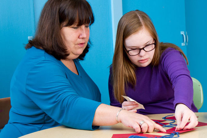 catechist and young person work on a craft project