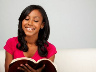 teen girl praying with the Bible