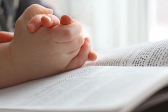 child's hands folded over the Bible