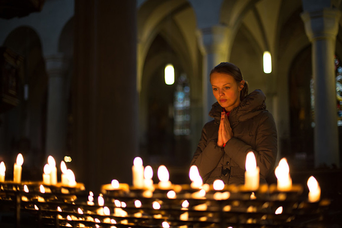 woman praying in church near candles