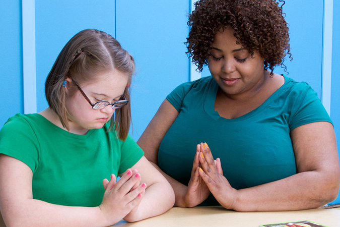 catechist and girl praying - © Loyola Press. All Rights Reserved.