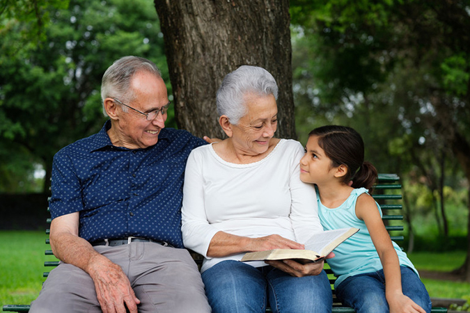 grandparents with granddaughter reading on park bench - aldomurillo/E+/Getty Images